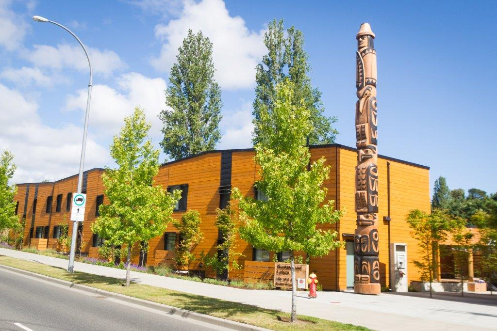 Yellow building with trees and totem pole