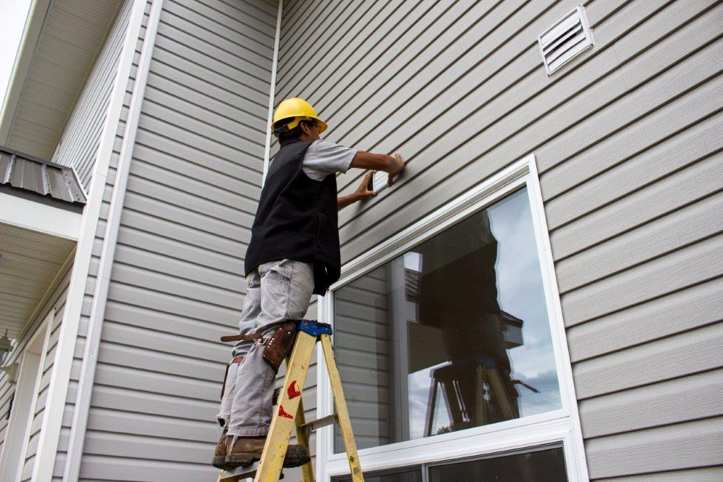 Man on a ladder leveling plastic vinyl siding on a grey house