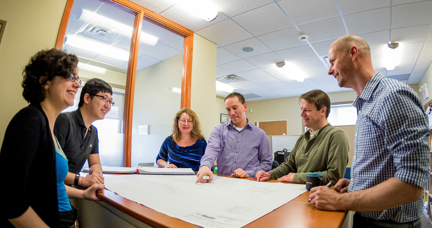group of people around a table discussing architectural plans