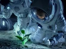 astronauts growing a plant on a planet's surface